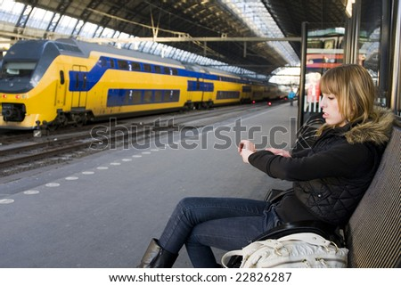 Young Woman at Train Station Looking at Watch - stock photo
