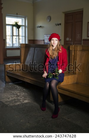 Young woman at train station with white rose  - stock photo