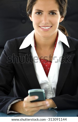 Young woman at workplace. She is a brown hair and brown eyes pretty businesswoman using phone at the office and she looks at camera. She wears a black formal jacket over a white shirt. - stock photo