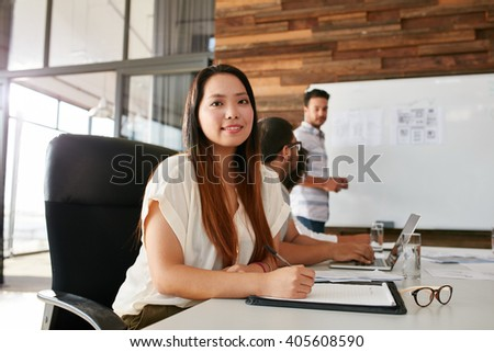 Young woman attending a business presentation in conference room with her colleagues in office. Asian woman looking at camera during presentation. - stock photo
