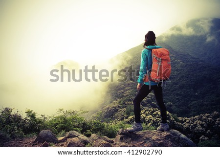 young woman backpacker at spring forest mountain peak