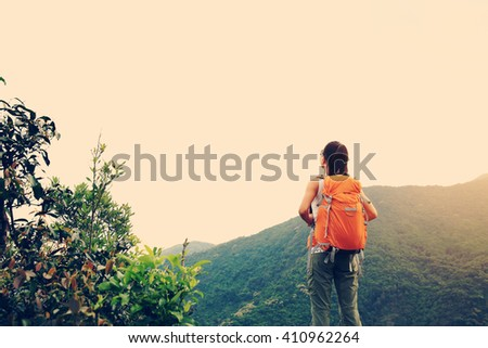 young woman backpacker hiking in spring forest mountain peak