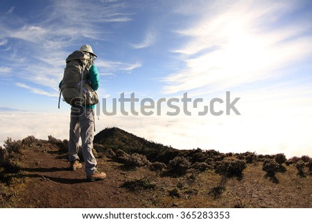 young woman backpacker hiking on mountain peak