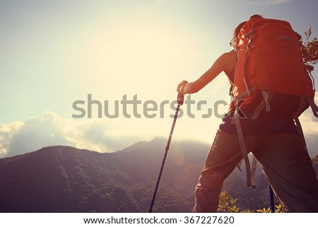 young woman backpacker hiking on mountain peak  - stock photo