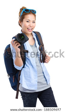 Young woman backpacker holding camera