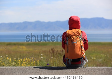 young woman backpacker sit on roadside taking a rest face the beautiful landscape