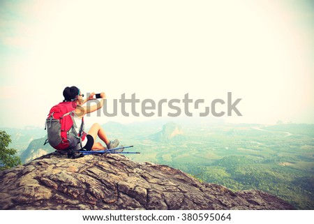 young woman backpacker taking photo with cellphone on mountain peak