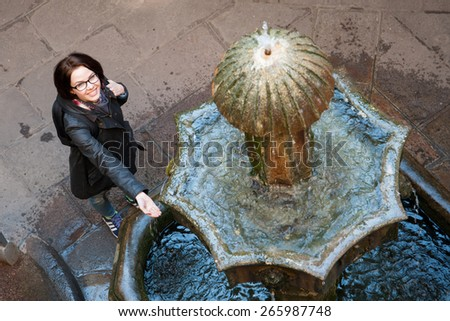 Young woman backpacker tourist in Europe looking the fountain in Barcelona, Spain - stock photo