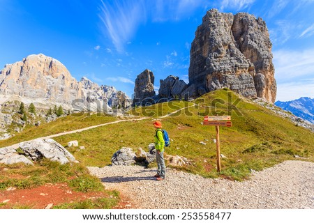 Young woman backpacker tourist on mountain trail near Cinque Torri rock formation, Cortina d'Ampezzo, Dolomites Mountains, Italy