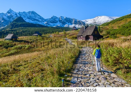 Young woman backpacker walking on mountain trail in Gasienicowa valley in autumn season, High Tatra Mountains, Poland - stock photo