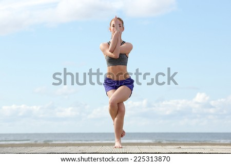 Young woman balancing in yoga position at the beach - stock photo