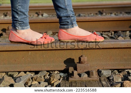 young woman balancing on rail track, detail - stock photo
