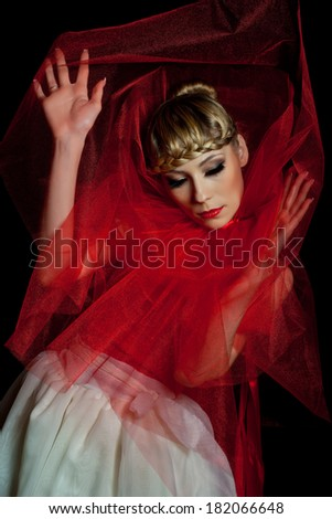 Young woman ballet dancer in red and white dress posing on black background