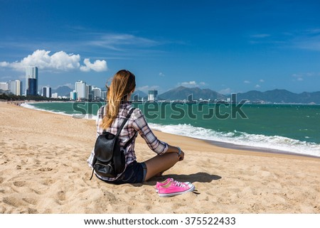 Young woman barefoot on the beach relaxing in yoga pose