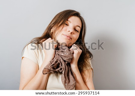 Young woman basking in the scarf. On a gray background. - stock photo