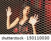 Young woman behind a metal fence - stock photo