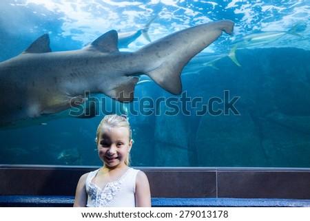 Young woman behind a shark tank looking at camera at the aquarium - stock photo