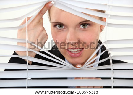 young woman behind blinds - stock photo