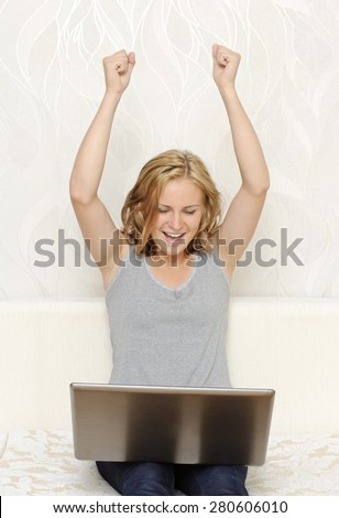 Young woman being happy and putting hands up - stock photo