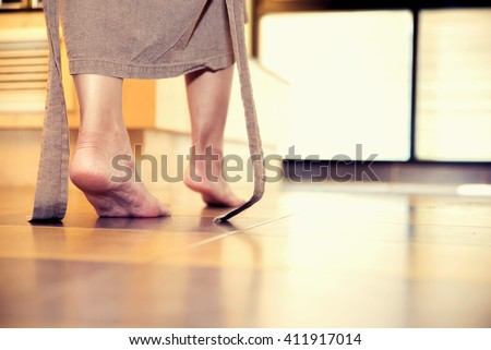 young woman being walking on the tiled floor in bathroom - stock photo