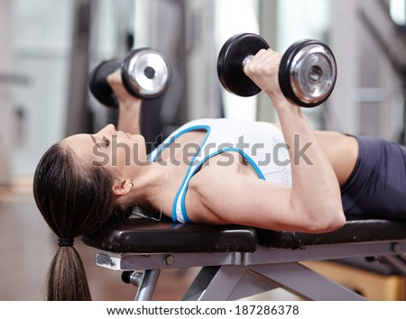 Young woman bench pressing with dumbbells in the gym, working triceps and chest - stock photo