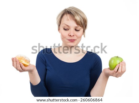 Young woman between donut and apple, isolated on white - stock photo