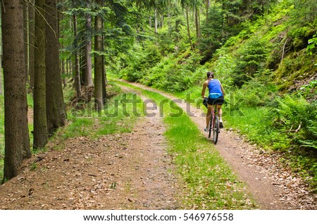 Young woman bicycling in the woods