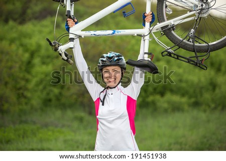 Young woman biker hold her bike up happy smiling outdoor. Cross country female biker relaxing after riding a bike - stock photo