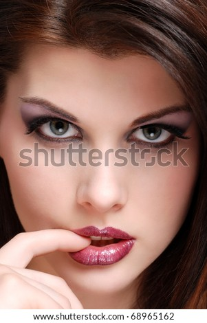 young woman biting her finger - stock photo