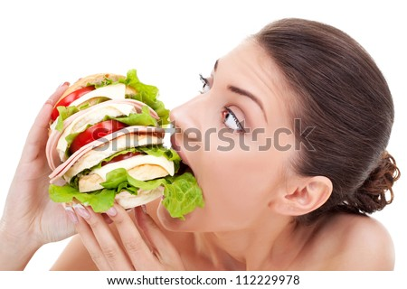 Young woman biting into a very big homemade bread roll filled with tomato and bacon on a white background