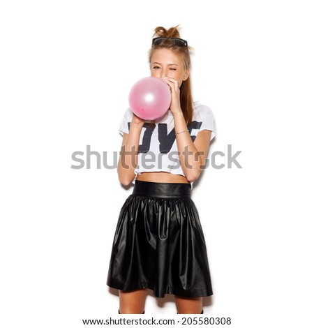 Young woman blowing a pink balloon . White background, not isolated - stock photo