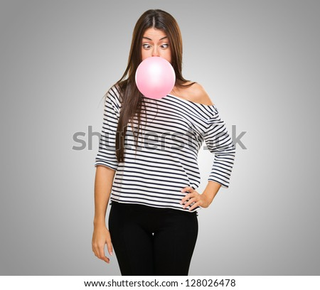 Young Woman Blowing Bubblegum and crossing her eyes against a grey background - stock photo