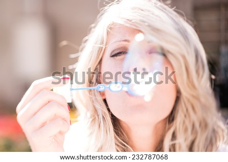 Young woman blowing bubbles - stock photo