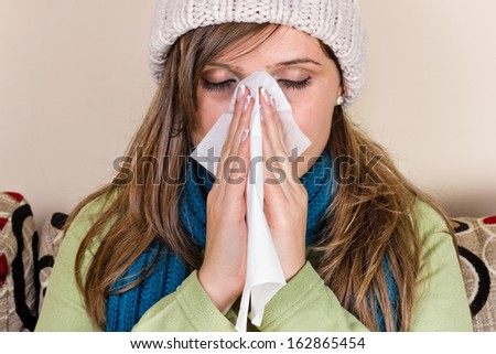 Young woman blowing her nose, feeling bad, at home