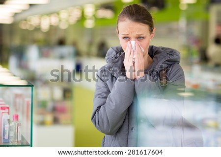 Young woman blowing her nose while in a modern pharmacy, choosing pills to help her with the flu/cold (shallow DOF; color toned image) - stock photo