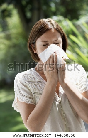 Young woman blowing nose with tissue paper in park