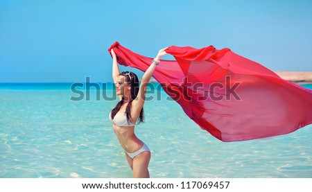 young woman blowing red cloth fabric in the breeze of a summer day