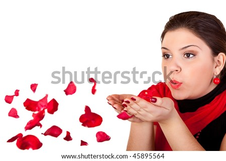 young woman blowing rose petals from her hands