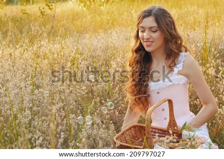 young woman blowing soap bubbles in the field