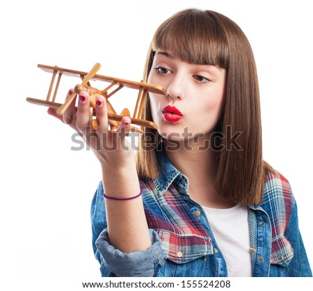 young woman blowing to a wooden airplane on white background
