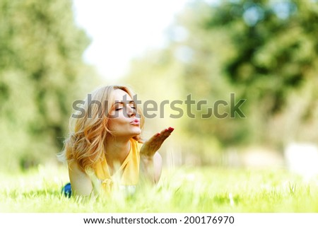 Young woman blows a kiss lying on green grass meadow