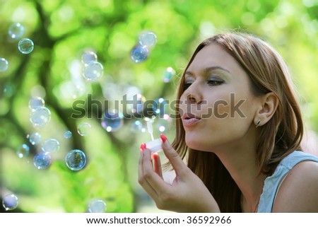 young woman blows soap bubbles in park