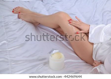 Young woman body care cream is applied on legs. Sitting on bed by putting cream on white bed sheets