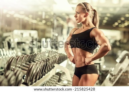 Young woman bodybuilder in gym. - stock photo