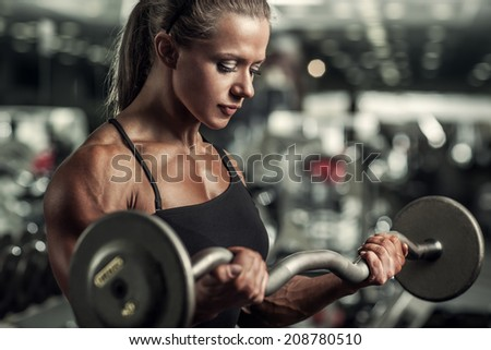 Young woman bodybuilder with barbell. - stock photo