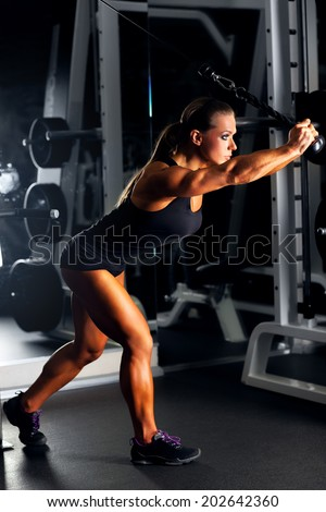 Young woman bodybuilder working with trainer. - stock photo