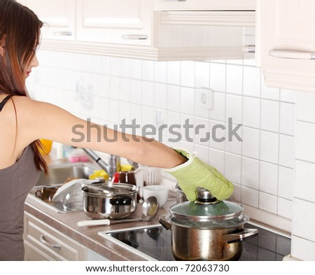 Young woman boiling something in pot (preparing dinner)