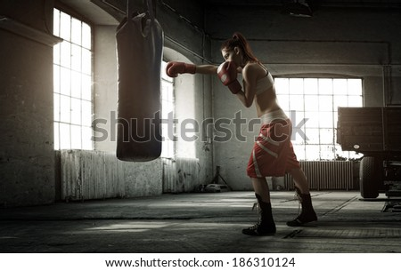 Young woman boxing workout in an old building - stock photo