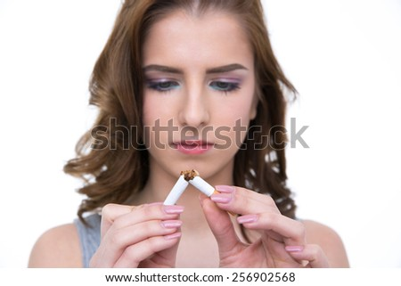 Young woman breaking cigarette and no smoking concept. Focus on cigarette - stock photo