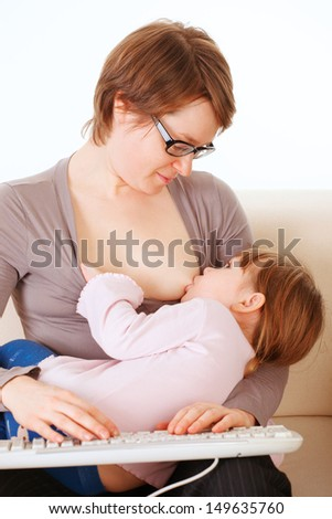 Young woman breastfeeds her baby and typing on the keyboard - stock photo